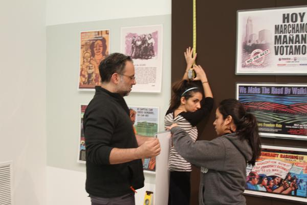 ART EXHIBIT: Students Anai Cosenza and Lavinia Aghakhani assist director David John Attyah to install the latest exhibit at the Art Gallery