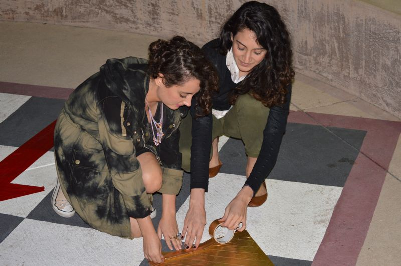 Maral Janoyan and Sarina Tounian work on the final touches for their sculpture project.