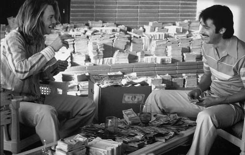 George Jung (Johnny Depp), left, and Diego (Jordi Molla) sit in their apartment surrounded by their ill-gotten gains.