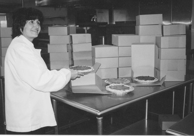 Janet Ghooks packages pies for a Culinary Arts Club fund-raiser.