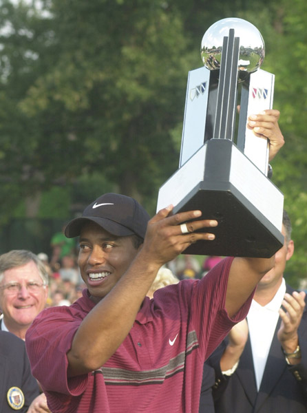Associated Press Tiger Woods holds up the winners trophy after winning the Buick Open at Warwick Hills in Grand Blanc, Mich., Sunday with a 15-under 201.