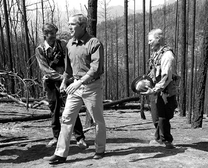 Bruce Ely/Associated Press President Bush, center, tours an area burned by the Squires Peak fire near Ruch, Ore., Thursday. During his visit, Bush argued that more logging in national forests would help prevent devastating wildfires.