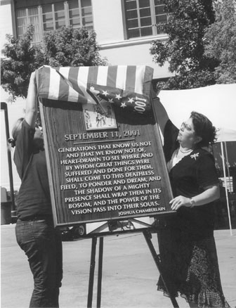 Edit Keshishian, vice President of campus activities, left, and President of the Board of Trustees Dr. Armine Hakopian unveil the Sept. 11 plaque.