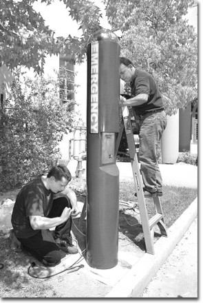 Photo by Cynthia Perry  Doug Aragon, of TRE Communications, installs one of eight emergency phones planned for the campus in the next few months.