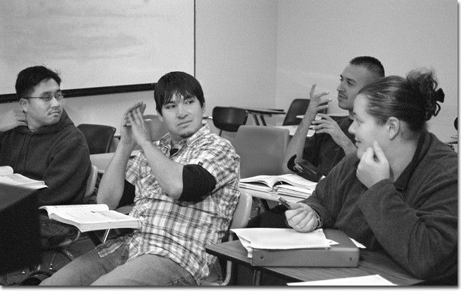 READ THE SIGNS — Javier Torres, left, converses with Regina Tsizer in their English grammar class.