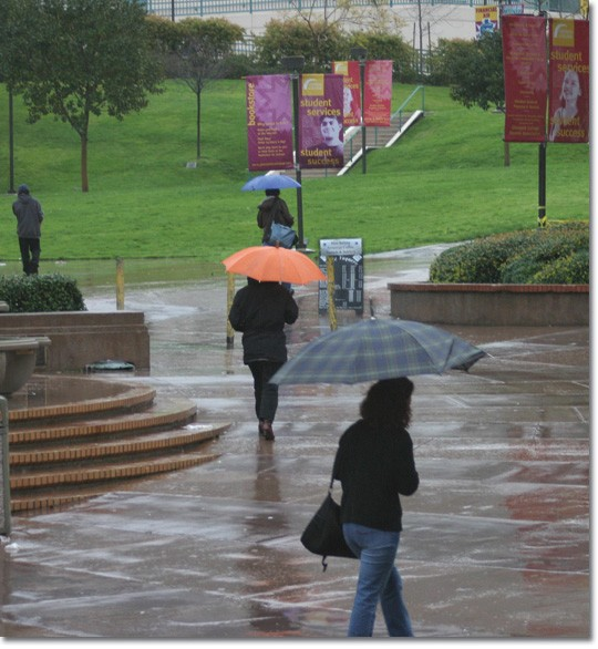 STUDENT DODGE PUDDLES AND MUD — Getting to classes on time is harder than usual because of the heavy rain.  A record rainfall of approximately 35 inches caused a mudslide that closed campus during winter session.