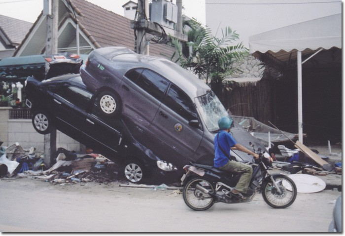 AWSOME POWER — A motorcyclist surveys the damage caused by a tsunmami that struck Thailand following a magnitude 9.0 earthquake.