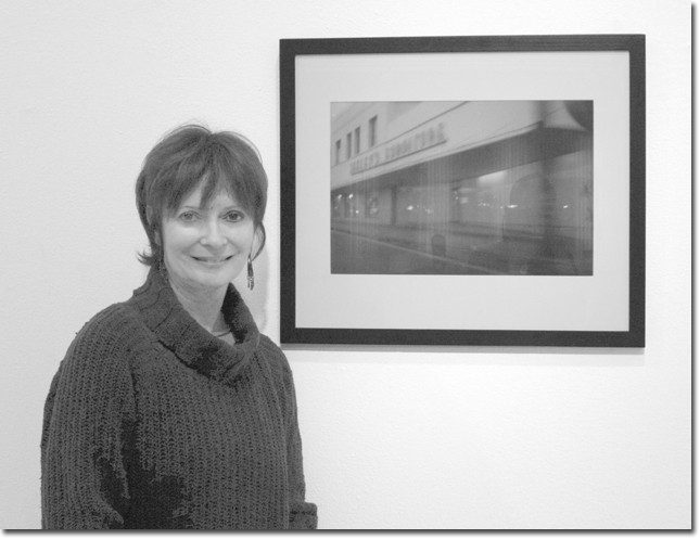 Arlene Vidor stands before one of her many photographs on display.