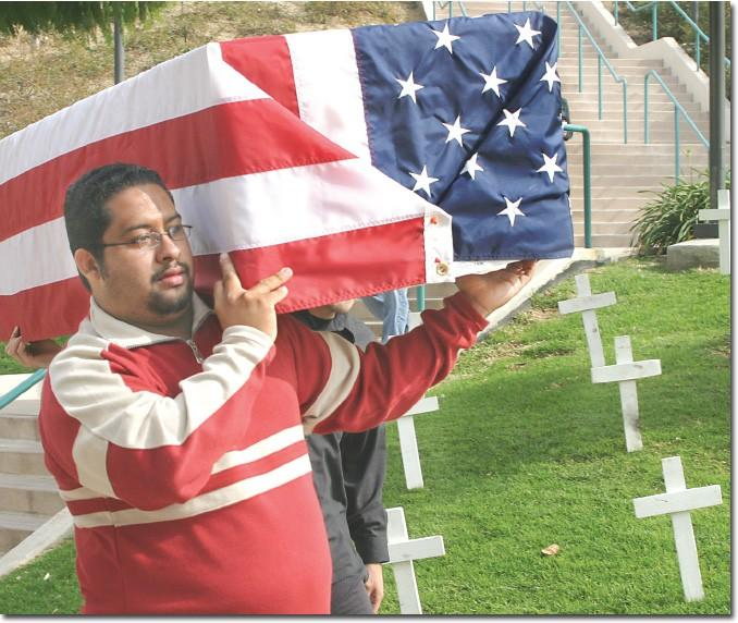 By placing a symbolic coffin in Plaza Vaquero, Joey Melendez, 24, a biochemistry major, sends a message about the consequences of the Iraq War.