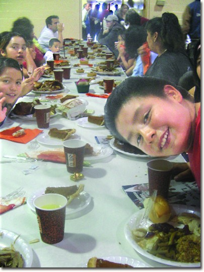 Miguel Gomez, 8, and his extended family from Pasadena, enjoy Thanksgiving dinner at the Salvation Army in Glendale.