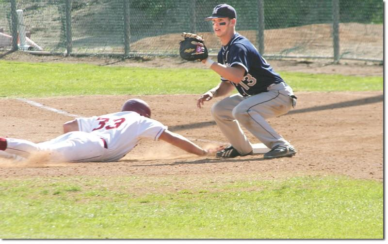 After hitting a solid base hit up the middle, outfielder Graham Miller quickly slides to first base to avoid the tag.