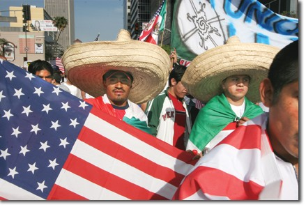 Protestors wave the Mexican and American flags during