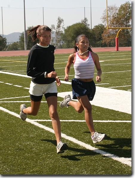 Ana Rodriguez, left, and Lily Hernandez warm up on the turf before joining the rest of their team to train for the Santa Barbara Invitationals.