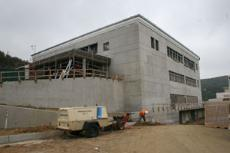 Construction personnel work around the clock to finish the new building which is scheduled to open in August.