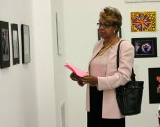 President/Superintendent Audre Levy admires a couple of photography pieces during the artists reception on May 17.