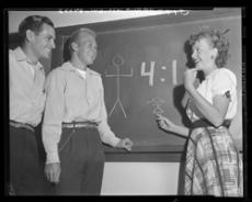 ILLUSTRATING HER POINT - Shirley Mae Dyson illustrates on a Glendale College blackboard her point that there are four men for every girl oncampus and that the school has good reason to add vocational studies to coeds' curriculum. Listening to her argument