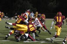 PILEUP ON THE FIELD: Reinaldo Reyes (18), Joey Orlandini (46),  and Keith Geines (11), get airborn in their attempt to stop Pasadena's Daniel Alvarado (99) on the final game of the season against cross-town rival, Pasadena City College.
