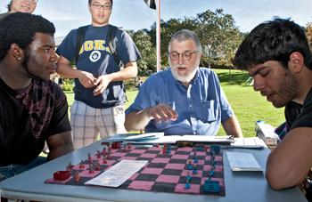 SMITING ALL COMERS: John Paul Bakshoian, center, also known as Shadow Hex, introduces his new chess variant, Fantasy Chess, to Glendale in this exhibition match. Fantasy Chess combines traditional chess with a layer of wargaming rules added on top.  All t