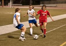 WALK THE PLANK: Lady Vaquero Sharis A. Harootun, dribbles past two Santa Monica defenders as she positions herself for an attempt on goal. Although Glendale played a tough game, they lost the match 4-0.