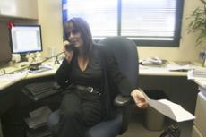 OFF THE CLOCK: Andra Verstraete, Director of Student Employment, answering a phone call amid taking questions about the recent hour reductions among student workers at Glendale Community College.