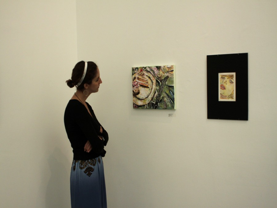 STUDENT ART: Tanalee Moore, a media arts major, admires a piece of artwork on Tuesday, displayed at the  student exhibit in the GCC Art Gallery.