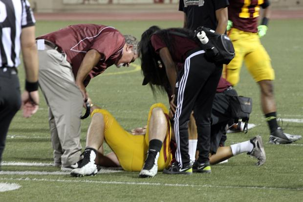 TAKEN OUT: Coach John Rome,left, rushes over to check on QB Grant Kraemer (No.15) after taking a brutal tackle that took him out of the game in the first quarter.