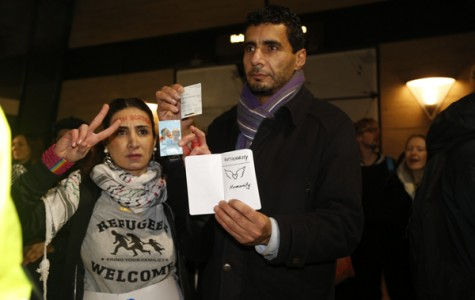 """ACTIVISTS: Toktam Johangiry and Salim Azi hold fake passports that read """"Nationality: Humanity"""" at the Jan. 9 protest event."""