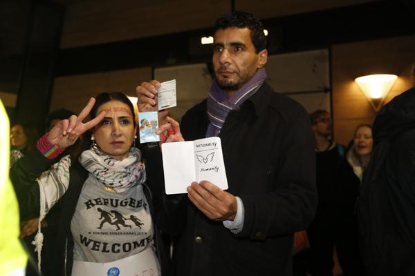 "ACTIVISTS: Toktam Johangiry and Salim Azi hold fake passports that read ""Nationality: Humanity"" at the Jan. 9 protest event."