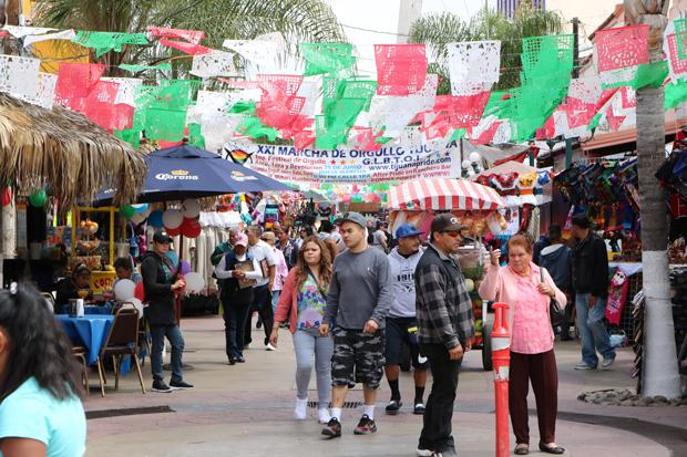 FIESTA: Tourists and residents walk around Zona Centro's market place in Tijuana, Baja Calif., Mexico, decorated with papel picado (tissue paper with intricate cutout designs) in the colors of the Mexican flag.