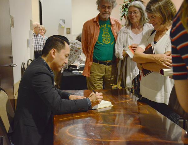 AUTOGRAPHS: Author Viet Thanh Nguyen signs books for fans after a reading in the Adult Recreation Center at the Glendale's Central Public Library on Sept. 29.