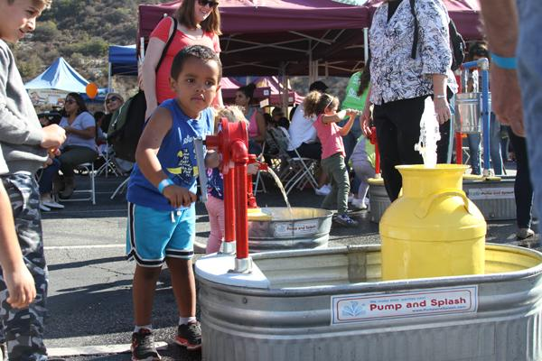 COOLING OFF:   Elijah Sowers, 3, enjoys the    water splash at the Parent/Student Association's Harvest Hoedown in the upper campus parking lot on Saturday.
