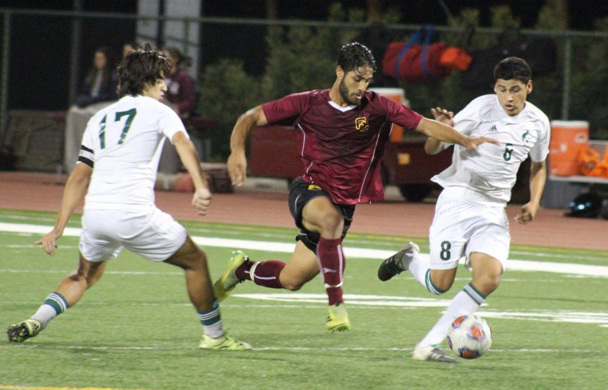 Freshman midfielder Loai Ibrahim breezes by two East Los Angeles defenders in the second half.