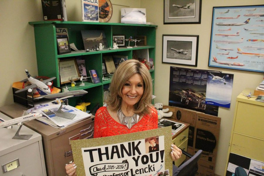 Sharon Lencki holds up a poster from a student thanking her for success in her flight