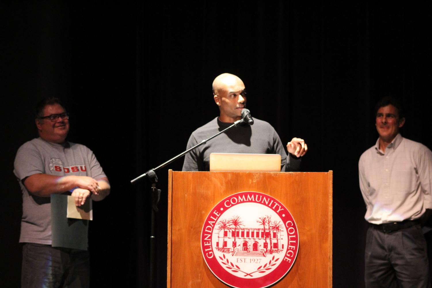 Kasan Butcher, flanked by counselor James Castel de Oro(left), and professor Joseph Beeman(right), gives his acceptance speech.