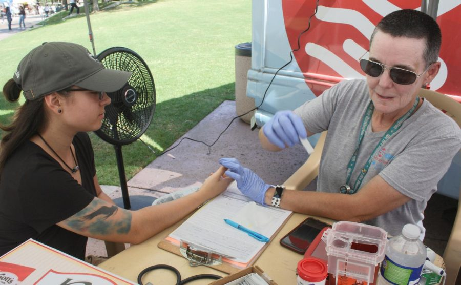 Technician Jackie Baca- Geary from the Huntington Hospital checks student Maja Herrera's Iron level, blood pressure, pulse, and temperature to see if she qualifies as a candidate to donate blood. The blood drive was located in the quad of Glendale Community College in Glendale, Calif.
