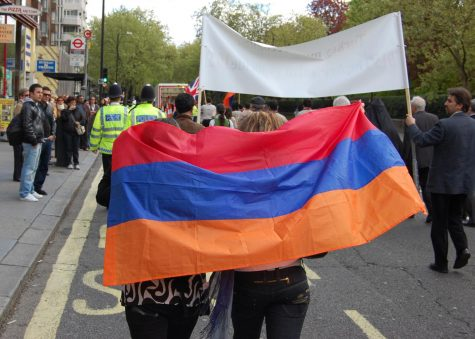 Two women holding an Armenian flag while participating in a commemorative march.