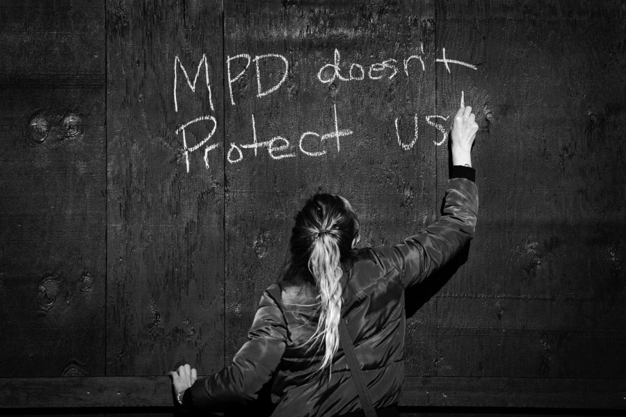 A protester writes 'MPD doesn't Protect Us' in chalk on a boarded up building near the Hennepin County Courthouse in downtown Minneapolis, Minnesota as the trial of former Minneapolis police officer Derek Chauvin began Monday morning.